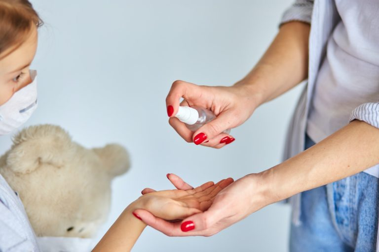 Mother and daughter using wash hand sanitizer gel.
